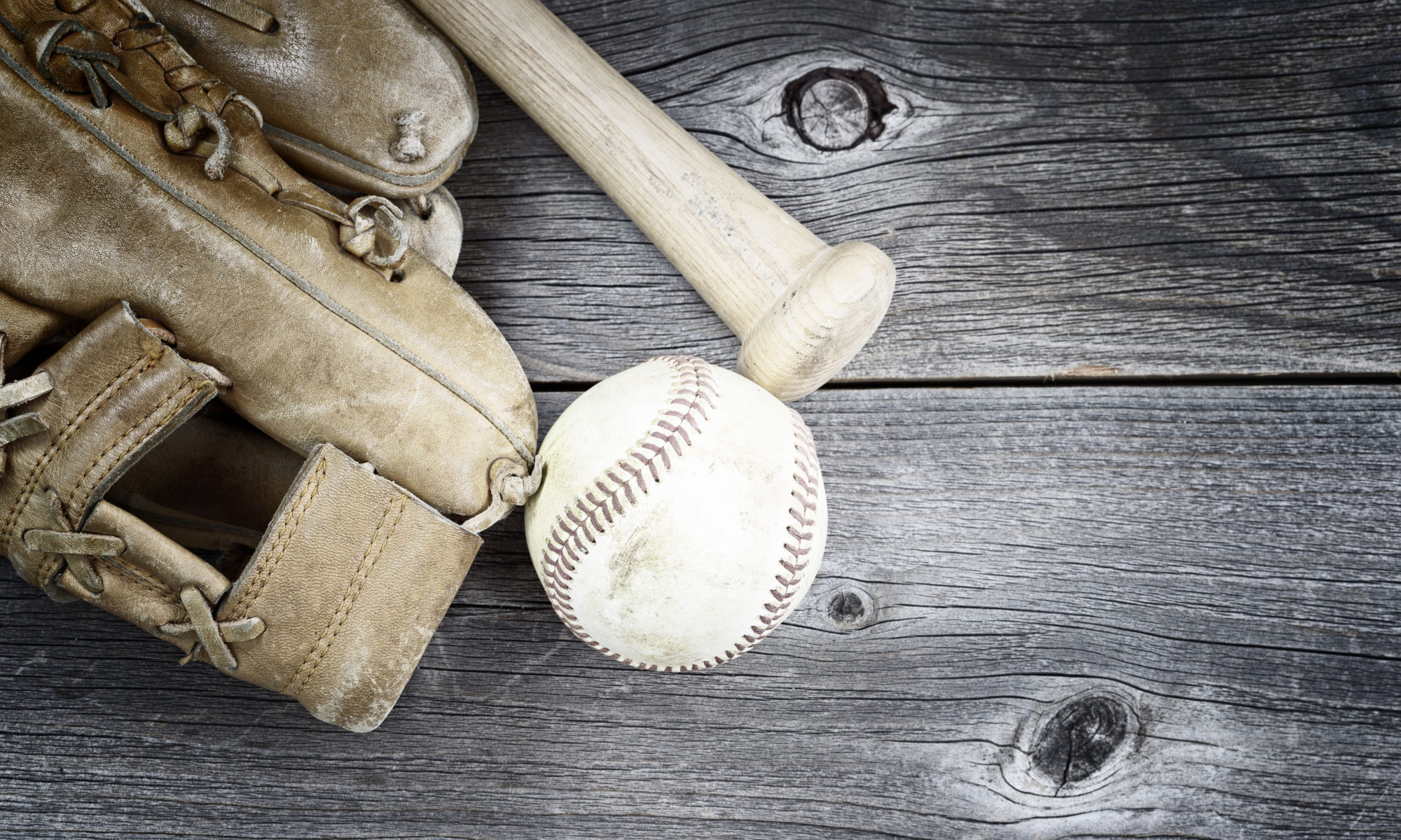 Vintage concept of old worn glove, bat and used baseball on rustic wood